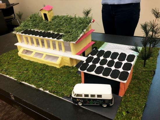 model of building and car with sustainable energy features like solar panels
