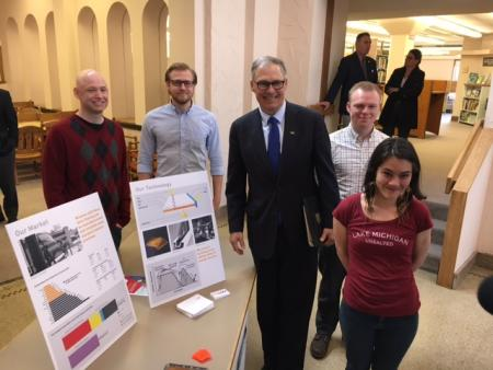 Governor Jay Inslee poses with students next to a table