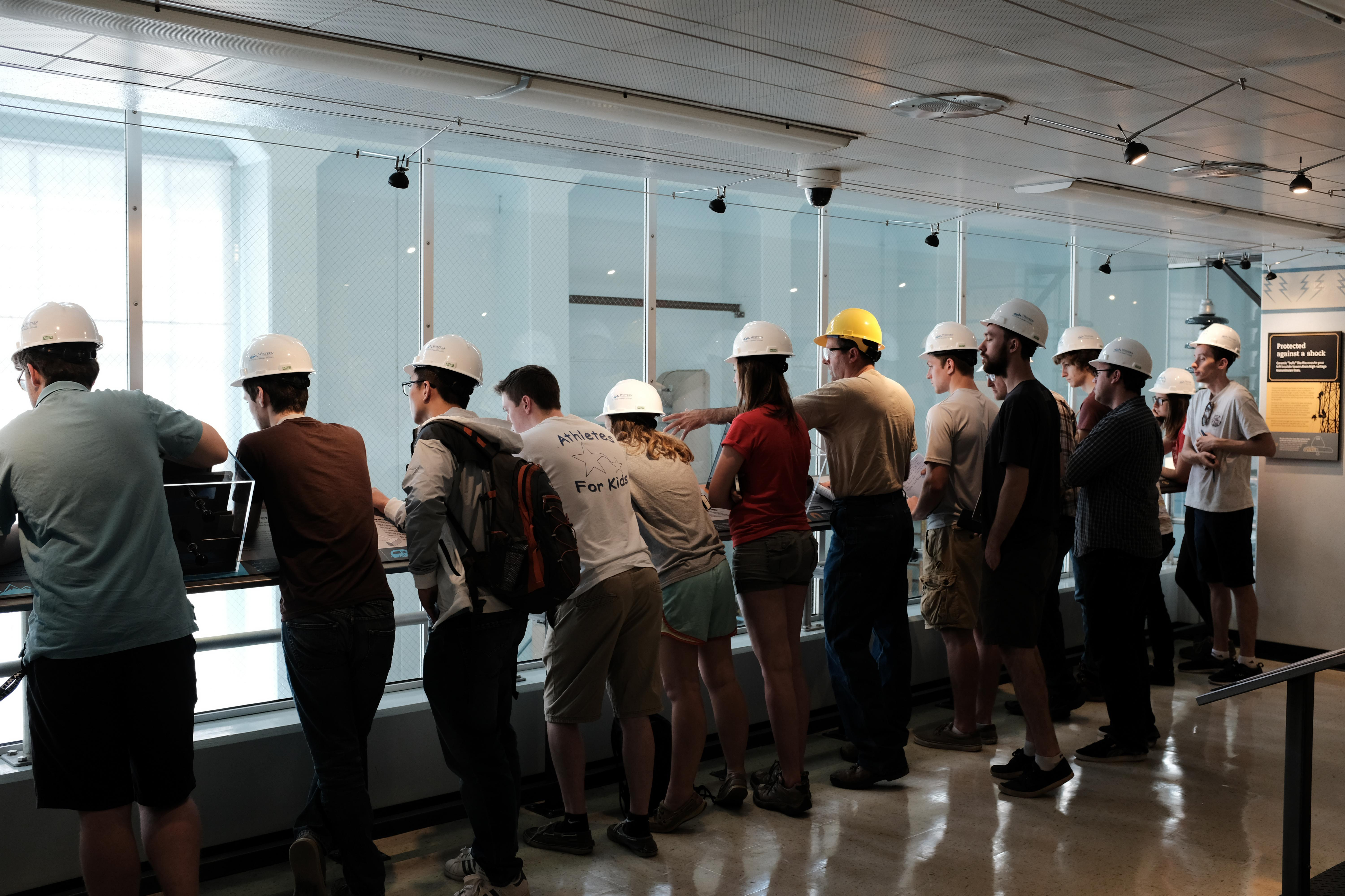 students wearing hard hats and looking over a railing