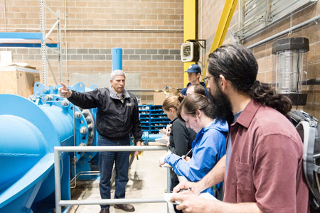 students looking at instructor standing in front of blue pipe