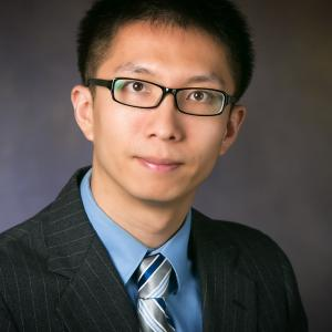 Xichen wears a suit jacket and tie, dark gray background
