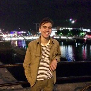 Leo smiling leaning against a rail wearing a brown jacket and striped shirt