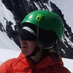 Deborah staring off into the distance wearing a green climbing helmet, and an orange coat standing on the mountaintop
